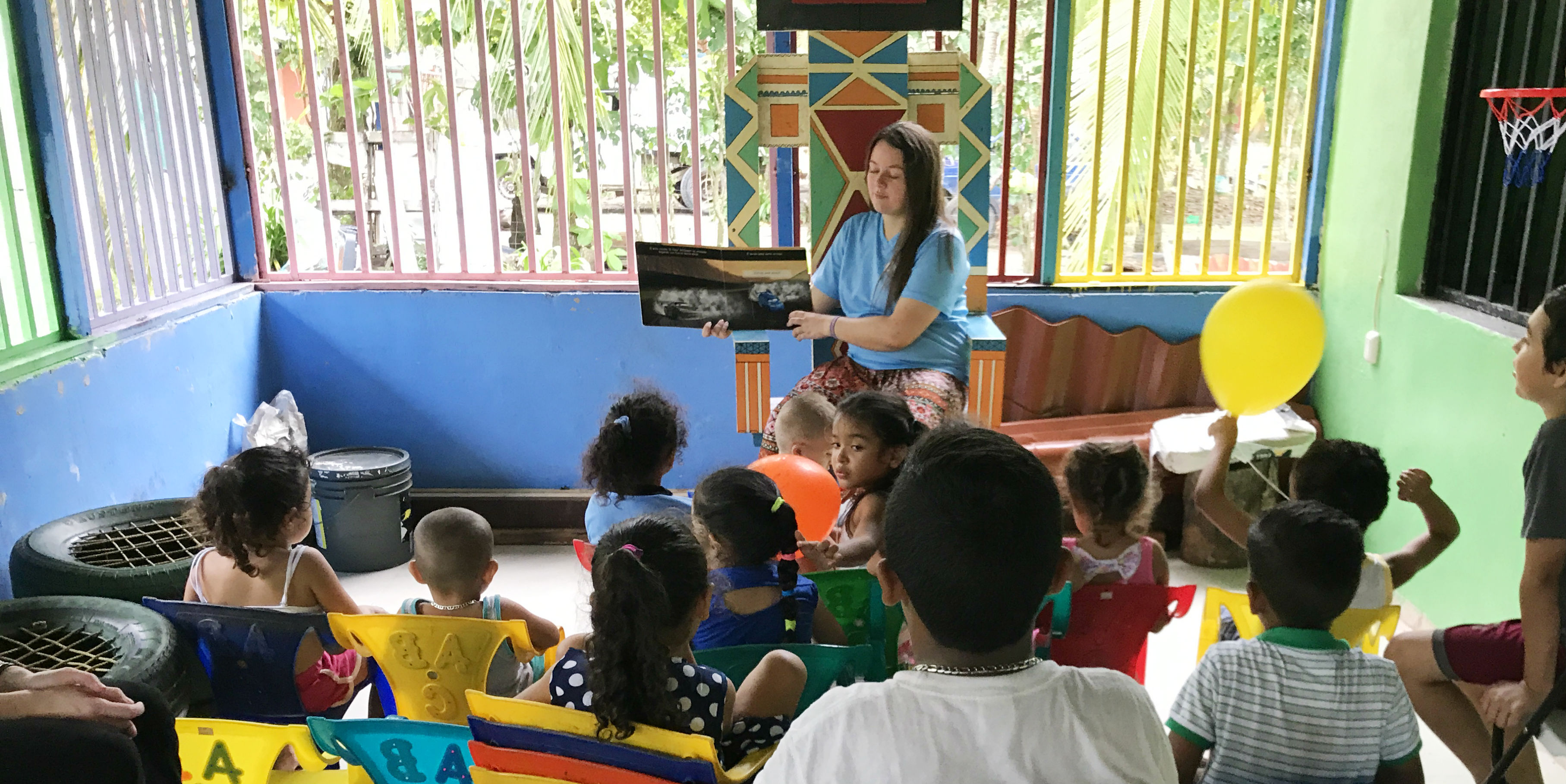 A GVI participant reads to learners in Quepos, Costa Rica. Teaching experience is one of the many gap year benefits.
