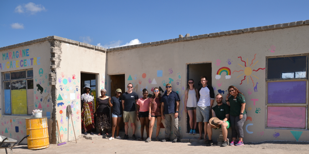 volunteers and locals standing outside a building