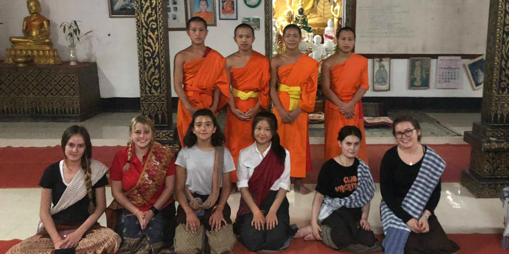 Volunteers kneeling in front of novice Buddhist monks in temple in Thailand.