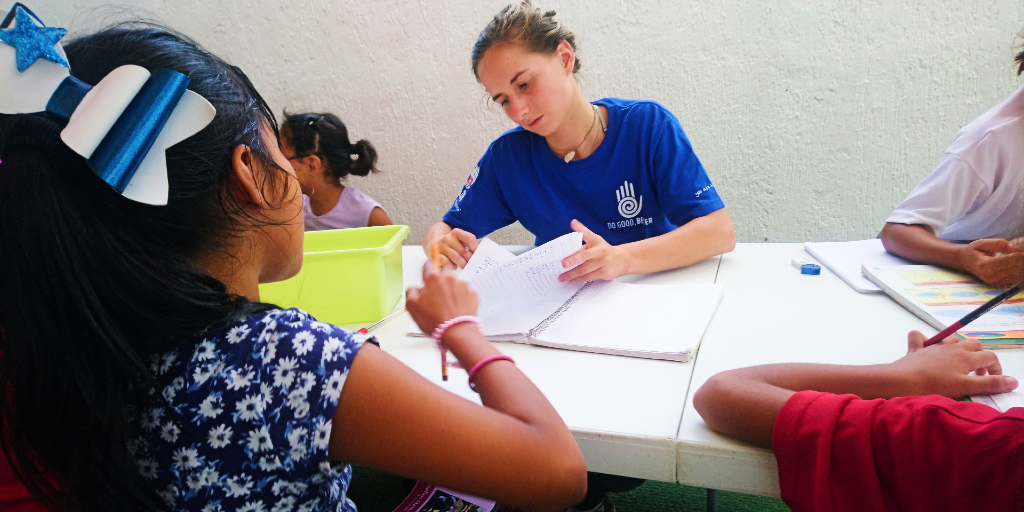 A lady helps a girl with her homework during a summer language immersion program.