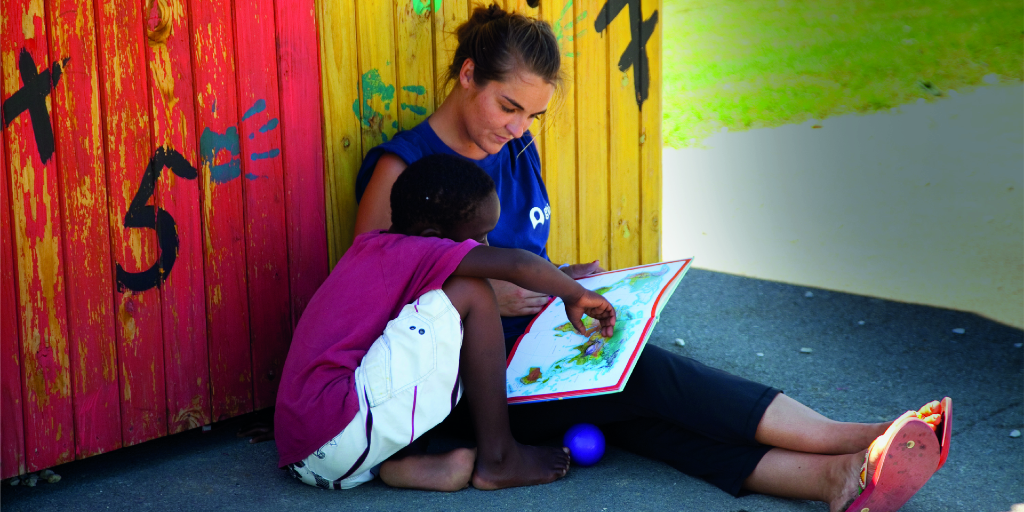 A Cape Town based GVI participant helps a child read.