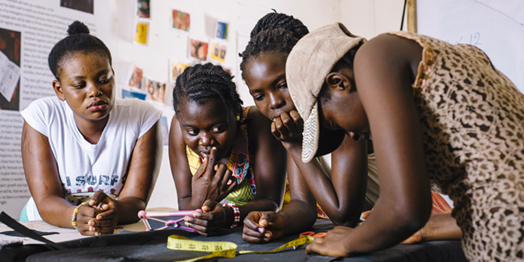Ghanaian women are working on a sewing project in order to improve their sewing skills.