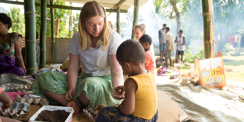 A GVI volunteer helps a child plant a seed for a gardening project.