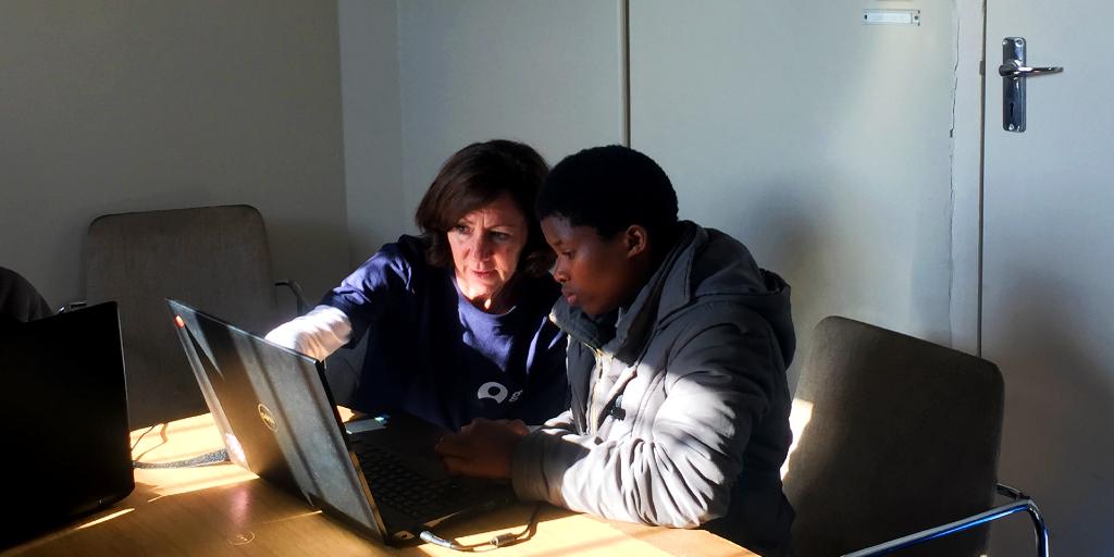 A GVI volunteer helps a women use a computer.
