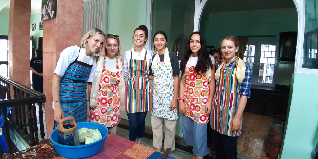 GVI 15 year old participants practice cooking local cuisine.