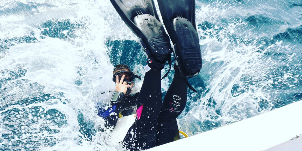 A GVI volunteer dives into the ocean.