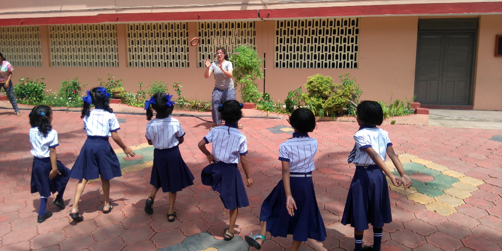 A GVI participant plays with the young girls at school.