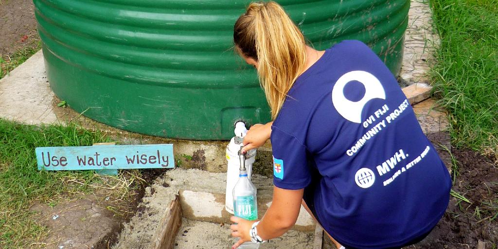 A GVI volunteer fills her water bottle with water.